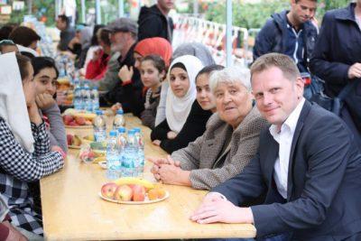 Tilo zusammen mit Jutta Schauer-Oldenburg am Tisch mit Flüchtlingskindern beim Fastenbrechen auf dem Vorplatz des Moabiter Otto-Spielplatzes (Foto: Gerald Backhaus)